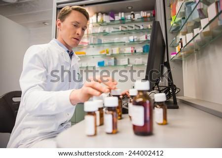 Pharmacist using computer at desk at the hospital pharmacy - stock photo