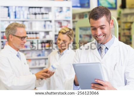 Pharmacist using the tablet at the hospital pharmacy - stock photo