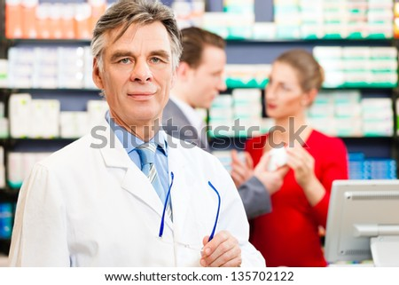 Pharmacist with customers in pharmacy, in the background are pharmaceuticals