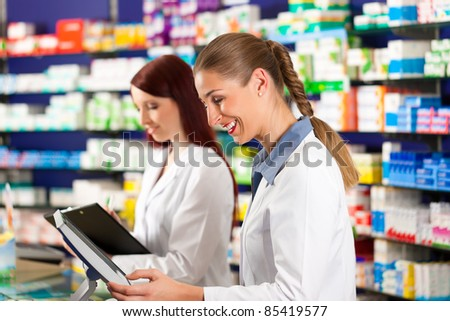 Pharmacist with female assistant in pharmacy standing at the cashpoint - stock photo