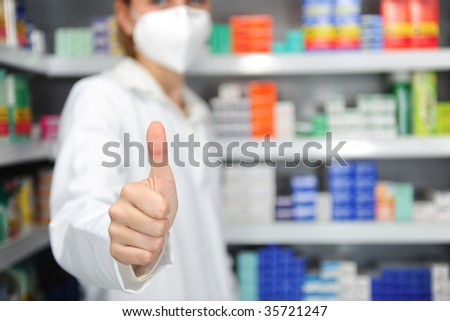 pharmacist with mask giving thumbs up - stock photo