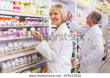 Pharmacists in lab coat looking at medicine in the pharmacy