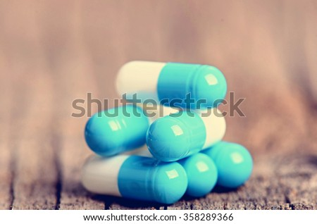 Pharmacy background. Pills on a wooden table. Medicine. Natural background. Capsule. Close up. Buildings from pills