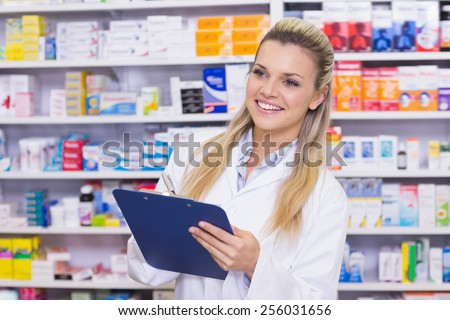 Pharmacy intern writing on clipboard at the hospital pharmacy - stock photo