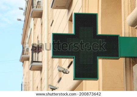 Pharmacy sign on the street. Green pharmacy cross on a background of the building. - stock photo