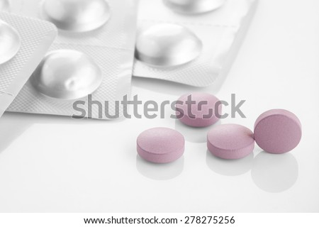 Pharmacy theme. Heap of purple round medicine tablet pills and blister - stock photo
