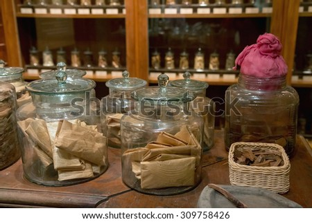 Pharmacy Traditional Chinese Medicine. Glass bottles with natural medicines on the table Chinese pharmacies. Natural medicine made from dried herbs in pharmacy shop. Therapeutic drugs from herbs.