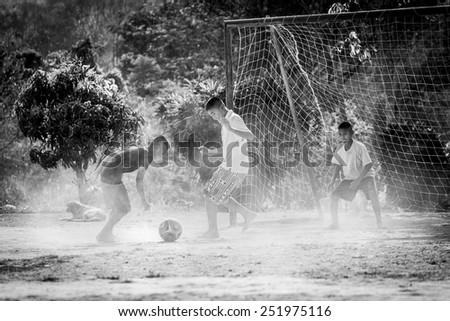 PHETCHABURI, Thailand - FEBRUARY 07, 2015: Karen hill tribel boy playing football in ground field in the school at Ban Bangkloy Phetchaburi, Thailand - stock photo