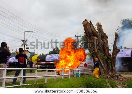 PHICHIT THAILAND-NOVEMBER 11:Flames from the fuel blaze near a big tree stump with fire officials, journalists and photographers.On November 11, 2015 in Phichit, Thailand.