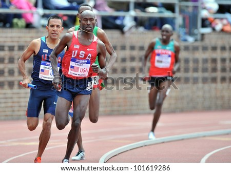 PHILADELPHIA - APRIL 28: Bernard Lagat and Leo Manzano are neck and neck in the final turn of the USA vs the World distance Medley at the Penn Relays April 28, 2012 in Philadelphia. - stock photo