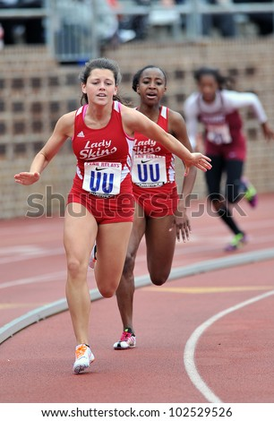PHILADELPHIA - APRIL 26: Kacey Cerankowski from Neshaminy HS (front) reaches back for the baton in a heat of 4x100 girls relays at the Penn Relays April 26, 2012 in Philadelphia. - stock photo