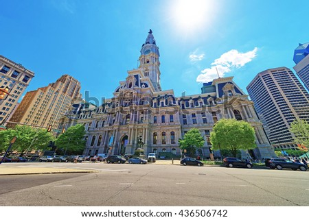 Philadelphia City Hall with William Penn figure atop Tower. View from the street. Tourists in the street. Pennsylvania, USA. With special sun flare - stock photo