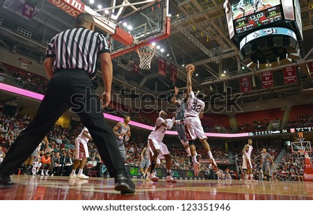 PHILADELPHIA - DECEMBER 31: An official watches the action as Temple and Bowling Green player battle in the lane during the basketball game December 31, 2012 in Philadelphia. - stock photo