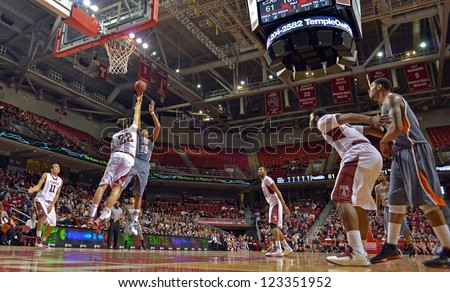 PHILADELPHIA - DECEMBER 31: Bowling Green Falcons forward/center Cameron Black (35) shoots as a Temple player defends during the basketball game December 31, 2012 in Philadelphia. - stock photo