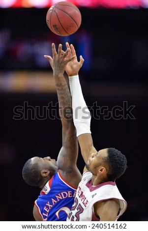 PHILADELPHIA - DECEMBER 22: Temple Owls forward/center Devontae Watson (23) jumps the opening tip against Kansas during the NCAA basketball game December 22, 2014 in Philadelphia.  - stock photo