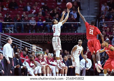PHILADELPHIA - FEBRUARY 26: Temple Owls guard Jesse Morgan (3) shoots a three pointer in front of his bench during the AAC conference college basketball game  February 26, 2015 in Philadelphia.  - stock photo