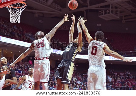 PHILADELPHIA - JANUARY 4: A pair of Temple Owls go up to block a shot during the American Athletic Conference basketball game January 4, 2015 in Philadelphia.  - stock photo