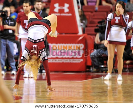 PHILADELPHIA - JANUARY 11: A Temple University cheerleader performs a back handspring during the AAC basketball game January 11, 2014 in Philadelphia.  - stock photo