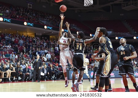 PHILADELPHIA - JANUARY 4: Temple guard Will Cummings (2) puts up a shot over UCF guard Calvin Newell (11) during the American Athletic Conference basketball game January 4, 2015 in Philadelphia.  - stock photo