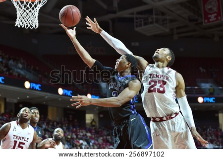 PHILADELPHIA - January 10: Tulsa Golden Hurricane guard Shaquille Harrison (3) shoots as a Temple defender tries for the block during the AAC  college basketball game January 10, 2015 in Philadelphia. - stock photo