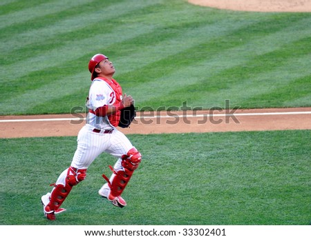 PHILADELPHIA - JULY 7: Philadelphia Phillies catcher Carlos Ruiz chases a foul ball in a game July 7, 2009 in Philadelphia. - stock photo