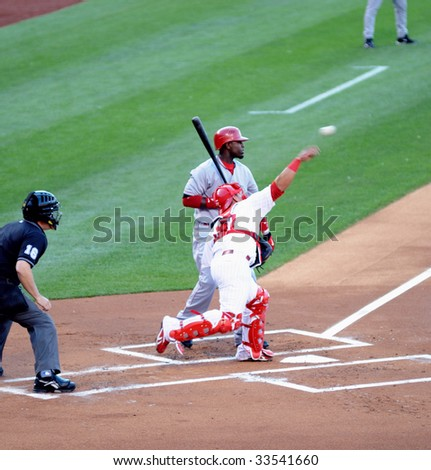 PHILADELPHIA - JULY 7: Philadelphia Phillies catcher Carlos Ruiz throws out a Reds baserunner during a game July 7, 2009 in Philadelphia. Reds second baseman Brnadon Phillips also pictured. - stock photo