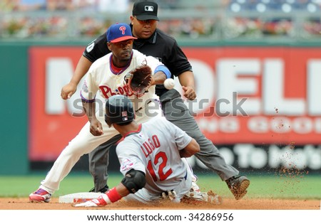 PHILADELPHIA - JULY 26: St. Louis Cardinals shortstop Julio Lugo slides in safely for a double during the July 26, 2009 game in Philadelphia. Phillies shortstop Jimmy Rollins receives the throw. - stock photo