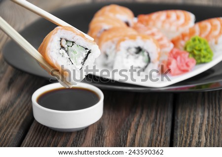 Philadelphia Maki on a black plate with ginger and wasabi with chopsticks - stock photo
