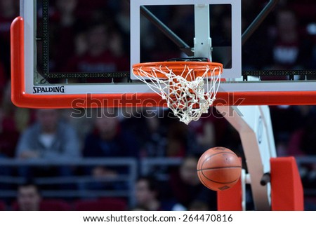 PHILADELPHIA - MARCH 25: A ball drops through the net and basket after a made free throw during the NIT quarterfinal basketball game March 25, 2015 in Philadelphia. - stock photo
