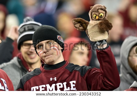PHILADELPHIA - NOVEMBER 8: A Temple Owls fan holds up an Owl puppet but looks dejected during the AAC football game November 8, 2014 in Philadelphia, PA.