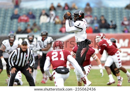 PHILADELPHIA - NOVEMBER 29: Cincinnati Bearcats wide receiver Mekale McKay (2) leaps to make a catch during the football game November 29, 2014 in Philadelphia. - stock photo