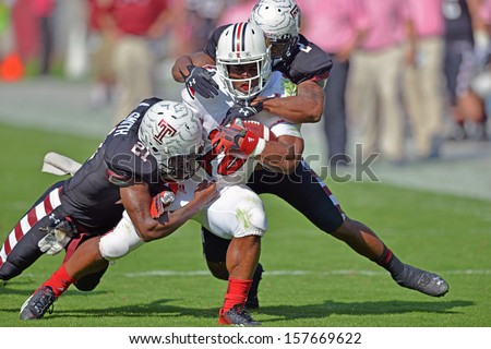 PHILADELPHIA - OCTOBER 5: Two Temple defenders tackle Louisville running back Michael Dyer (white jersey) during a AAC football game against Temple October 5, 2013 in Philadelphia - stock photo