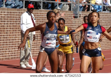 PHILADELPHIA, PA - APRIL 29: Hazel Clark takes handoff from Monica Hargrove on April 29, 2006 in Philadelphia.  They are on the 800-meter anchor of the USA Blue women's sprint medley relay  in the 112th Penn Relay - stock photo