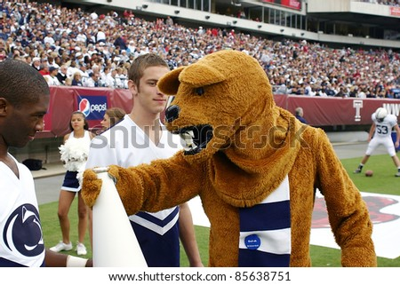 PHILADELPHIA, PA. - SEPTEMBER 17: Penn State cheerleaders on the sidelines with the Nittany Lion during a game against Temple on September 17, 2011 at Lincoln Financial Field in Philadelphia, PA. - stock photo