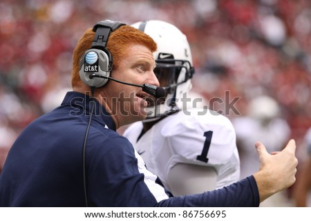 PHILADELPHIA, PA. - SEPTEMBER 17: Penn State coach Mike McQueary talks to QB Rob Bolden during a timeout in a game against Temple on September 17, 2011 at Lincoln Financial Field in Philadelphia, PA. - stock photo
