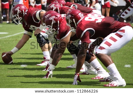 PHILADELPHIA, PA. - SEPTEMBER 8: Temple offensive linemen get ready to snap the ball against Maryland on September 8, 2012 at Lincoln Financial Field in Philadelphia, PA. - stock photo