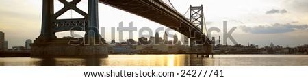 Philadelphia, PA skyline from Camden, NJ showing Ben Franklin Bridge at sunset. - stock photo