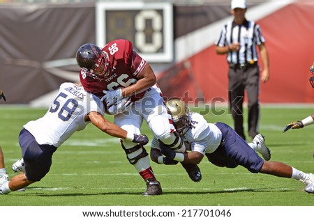 PHILADELPHIA - SEPTEMBER 6: Temple Owls'  Dion Dawkins #66 stumbles ahead after a rare reception for the o-lineman in a NCAA football game between Temple and Navy September 6, 2014 in Philadelphia.  - stock photo