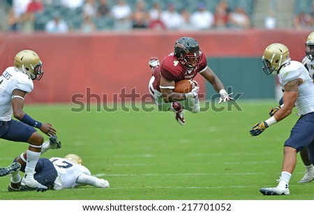 PHILADELPHIA - SEPTEMBER 6: Temple Owls running back Kenneth Harper #4 goes airborne after being hit during a NCAA football game between Temple and Navy September 6, 2014 in Philadelphia.  - stock photo