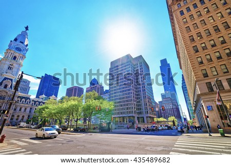 Philadelphia, USA - May 4, 2015: Penn Square with Philadelphia City Hall and skyline of skyscrapers. Tourists in the street. Pennsylvania, USA. With sun flare - stock photo