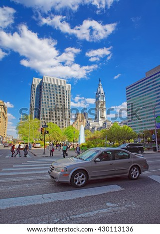 Philadelphia, USA - May 4, 2015: Philadelphia City Hall with William Penn sculpture atop the Tower. View from the street. Tourists in the street