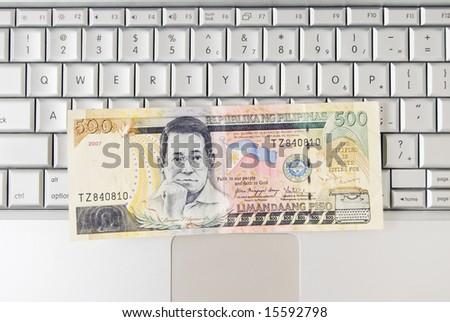 Philippine money on computer keyboard - stock photo