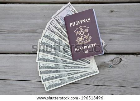 Philippine passport with US dollars  - stock photo