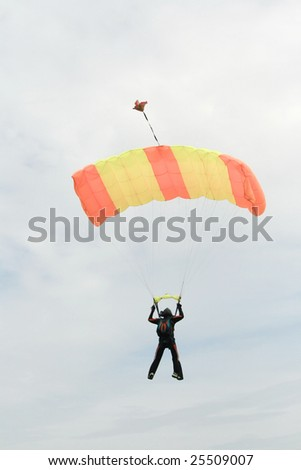 Philippines - February 14: a black  skydiver in orange and yellow parachute at the 14th Philippine International Hot Air Balloon Festival held  at Clark, Philippines