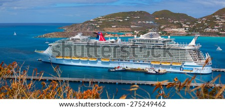PHILIPSBURG, SAINT MARTIN - MARCH 13, 2013: The biggest cruise ship in the world was docked in the central terminal. Over 5,500 guests went out to visit Exotic Island. - stock photo