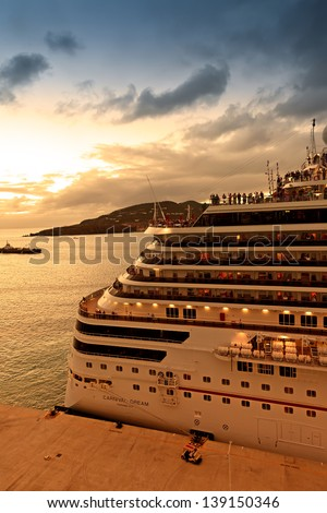 PHILIPSBURG, ST. MAARTEN - JAN. 16:  Passengers on The Dream enjoy the sunset view before departing from St. Maarten on Jan. 16, 2013. Carnival's Dream ship is one of their largest and newest ships. - stock photo