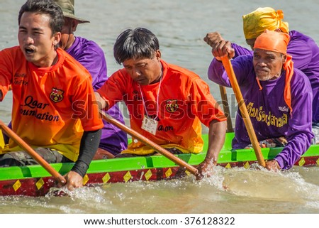 Phimai, Thailand - November 25, 2012: Fighting with passion for the team to win the annual Phimai Boat Race at the Moon River mearby the ancient Khmer City. - stock photo