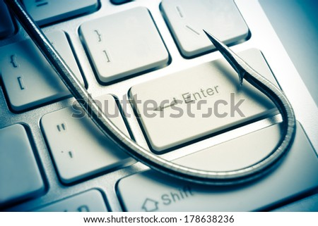phishing / a fish hook on computer keyboard / computer crime / data theft / cyber crime - stock photo