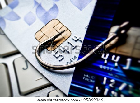 phishing / credit card phishing / computer crime / financial fraud / fish hook on a credit card - stock photo