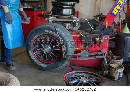 PHITSANULOK, THAILAND - DECEMBER 29 , 2016 :  Professional auto mechanic replacing tire on wheel in car repair workshop in Phitsanulok, Thailand